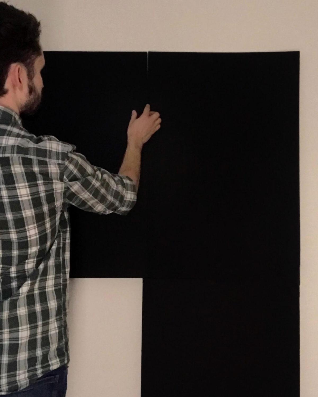 Man mounting black backdrop onto a wall